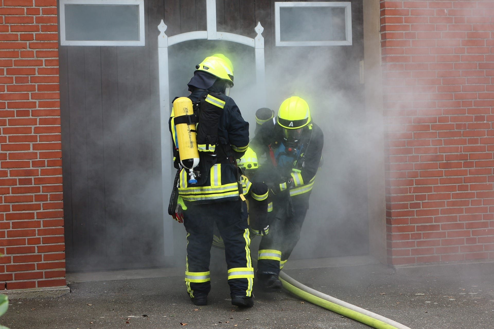 fire fighters in smoke filled building